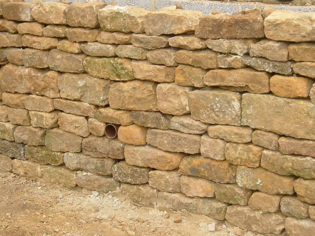 Drystone wall. Backfilled with block supporting wall and drainage